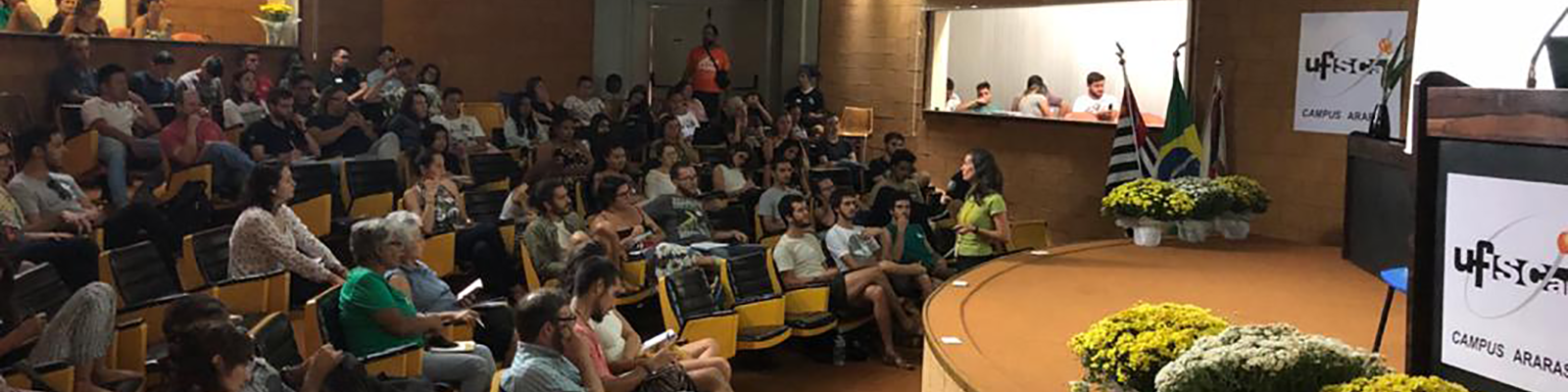 CCA-UFSCar's amphitheater with people sitting on orange coloured chairs with black seats, fixed on the side, stage with pulpit and flower pots. On the stage's edge, Brasil's, São Paulo's and Araras' (municipality) flags. On the ceiling, spotlights turned to the stage.